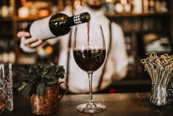 Bartender pouring red wine from a bottle in a wine glass, selective point of view on a wine glass