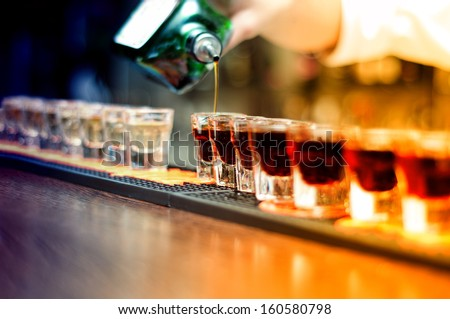 Bartender pouring strong alcoholic drink into small glasses on bar, shots