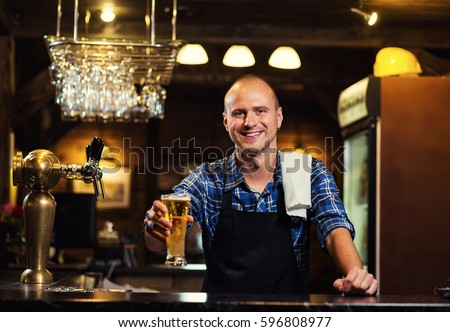 Bartender pouring the fresh beer in pub,barman hand at beer tap pouring a draught lager beer,beer from the tap,Filling glass with beer,fresh beer,pub.Bar.Restaurant.European bar.American bar. #596808977