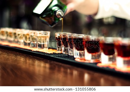 Bartender pours alcoholic drink into small glasses on bar
