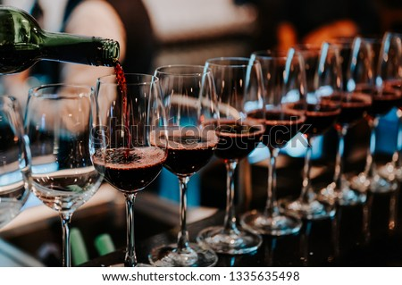 Bartender pours red wine in glasses at bar.Male sommelier pouring red wine into long-stemmed wineglasses.
