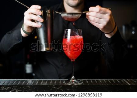 Bartender prepares Margarita cocktail, dark background, close-up #1298858119