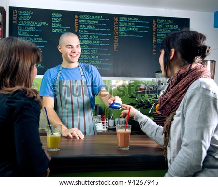 Bartender receiving credit card of customer for payment in cafe