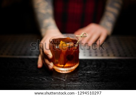 Bartender serving a glass of a Old Fashioned cocktail with orange zest on the bar counter on the blurred background