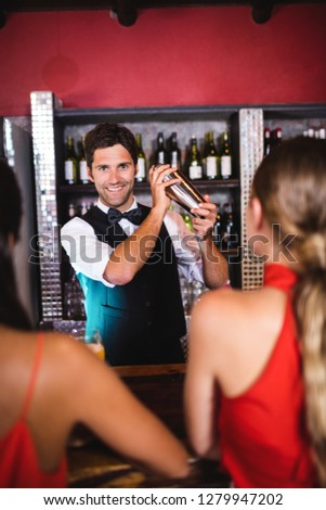 Bartender shaking cocktail in cocktail shaker at bar counter in nightclub #1279947202