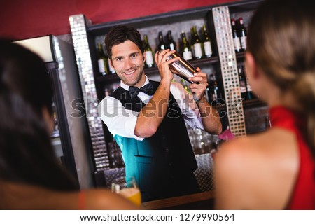 Bartender shaking cocktail in cocktail shaker at bar counter in nightclub #1279990564