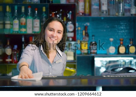 Bartender smiles, wiping the table with a rag at the hotel bar. Bartender in the workplace. Shelves with bottles of alcohol in the background. The concept of work and service. #1209664612