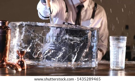bartender splits a block of ice to cool cocktails, barmen splitting huge clear ice block to two parts by using an ice pick and hammer.