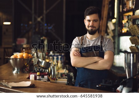 Bartender standing at bar counter, arms crossed. #645581938