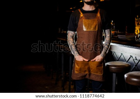 Bartender with tattoo on hand dressed in brown apron standing near the dark bar counter in night club #1118774642
