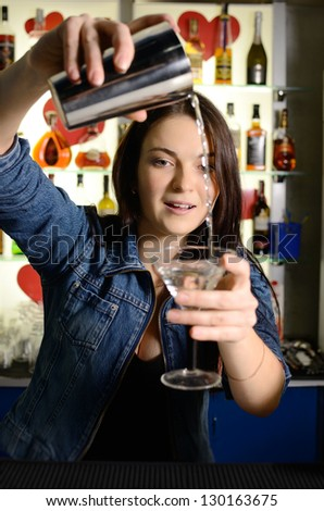 Bartender woman pours the cocktail into a glass