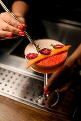 bartender woman's hand holds tweezers with green twig and decorates glass with frothy drink and flowers