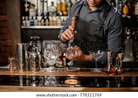 Bartenders`s hands crushing a big ice cube on the bar counter with a special bar equipment on it