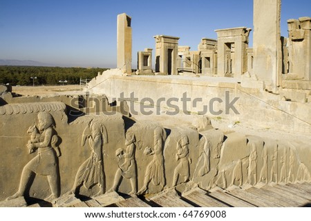 Bas-relief decoration along stairs from Darius palace to Palace of Xerxes, ruins of Daraius palace on the background.