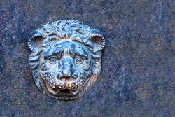Bas-relief of an ancient bronze lion on a marble slab. Bronze lion fountain