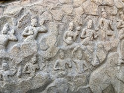 Bas relief stone carvings of historical sculptures on the monolithic granite rocky mountains at Mahabalipuram, Tamilnadu. India art of rock relief sculpture carvings in ancient temples.