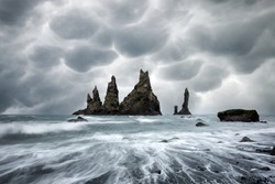 Basalt rock formations Troll toes on black beach with stormy sky with menacing mammatus clouds on background. Reynisdrangar, Vik, Iceland