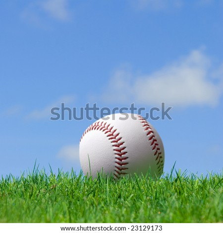 base ball in green grass field with blue sky background