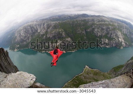 BASE jumper jumping off a big cliff in Norway with a red windsuit, breathtaking