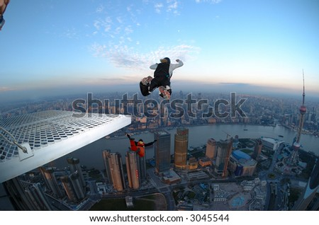 BASE jumper jumping off the Jin Mao Tower in Shanghai, China at sunrise