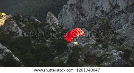 Base jumper under a bright red parachute flies against a background of a dark rocky landscape after jumping from the top of a mountain, view from above. Panorama.