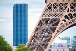 Base of the Eiffel tower with Montparnasse tower in background - Paris, France - Stock Image