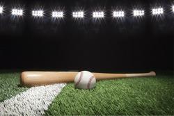 Baseball and bat at night under stadium lights on grass field with white stripe