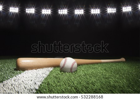 Baseball and bat at night under stadium lights on grass field with white stripe