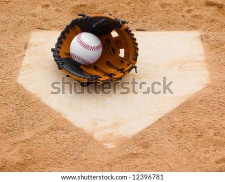 Baseball and glove set on home plate