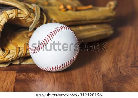 Baseball ball and baseball glove on wood background