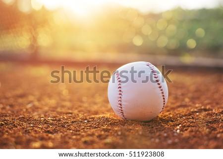 Baseball ball on pitchers mound. Baseball field at sunset