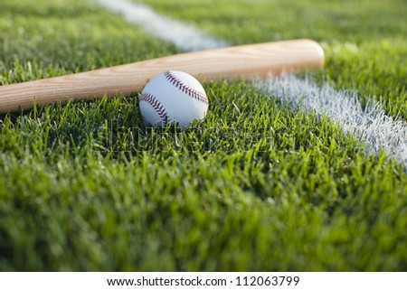 Baseball bat and ball near stripe on grass field