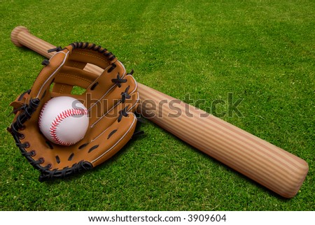 Baseball bat, ball and glove isolated on a field of grass