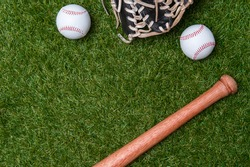 Baseball bat, glove and ball on green grass field.  Sport theme background with copy space for text and advertisment
