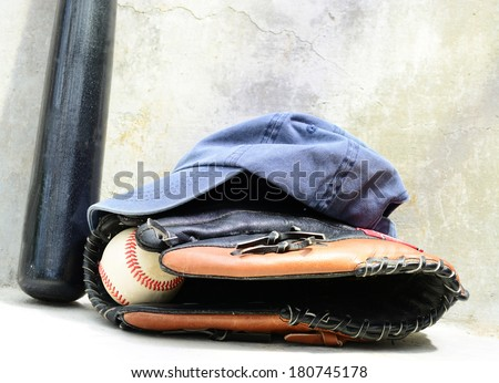 Baseball bat wit a cap and a glove with a ball in it