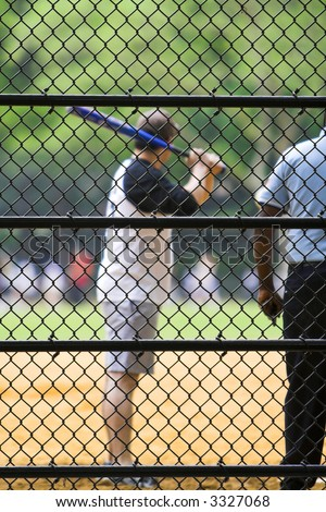 Baseball batter at the plate with focus on fence