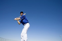 Baseball batter, in blue uniform, preparing to hit ball during competitive game, front view, low angle view (tilt)