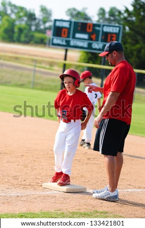 Baseball coach giving instruction to player at first base during a game.