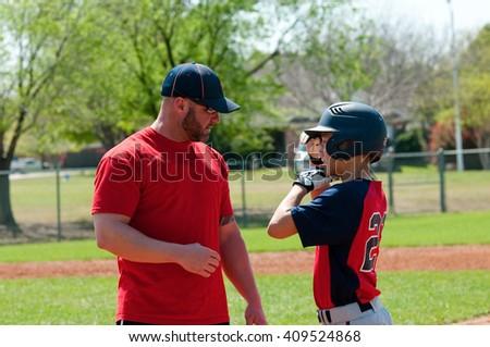 Baseball coach giving instruction to teen baseball boy.
