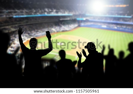 Baseball fans and crowd cheering in stadium and watching the game in ballpark. Happy people enjoying a match and sport event in arena. Friends watching ballgame live. #1157505961