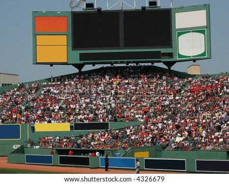 baseball fans sitting in stands under large signs