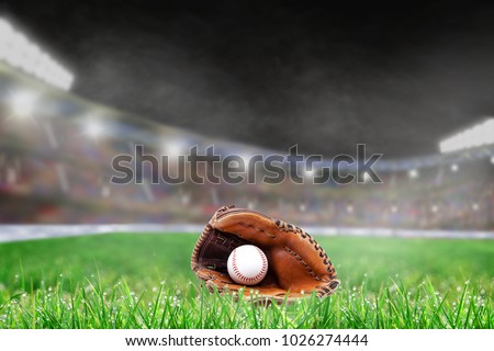 Baseball glove and ball on grass in brightly lit outdoor stadium with focus on foreground and shallow depth of field on background. Deliberate lens flare and copy space.
