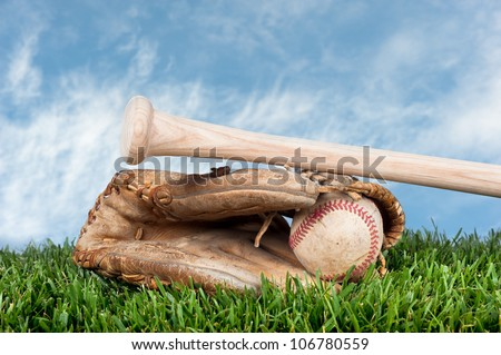 Baseball glove, ball, and bat laying on grass against a blue, lightly cloudy sky for placement of copy.
