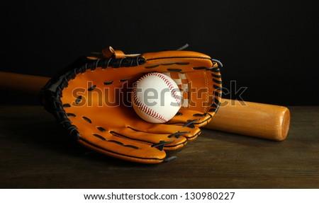 Baseball glove, bat and ball on dark background