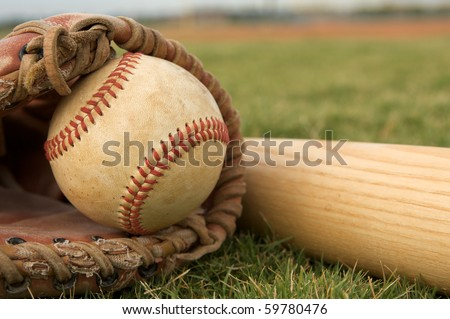 Baseball in a Glove near the Baseball Bat