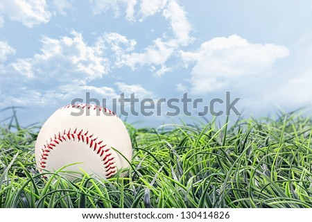 Baseball in lying in the grass on a beautiful summer day. - stock photo
