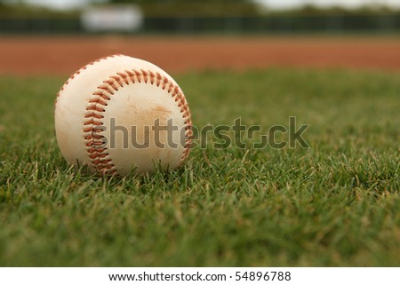 Baseball on the Grass with the field beyond - stock photo