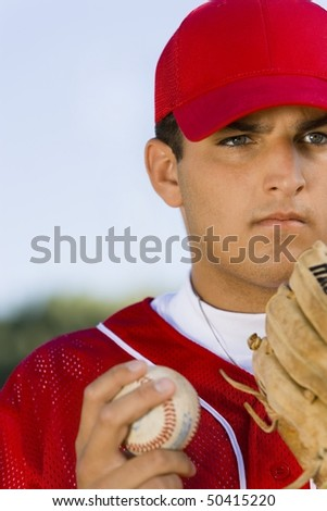 Baseball pitcher holding glove and ball, (close-up)