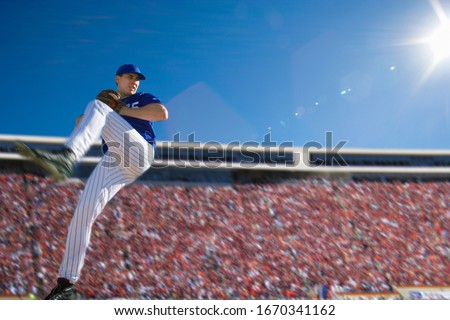 Baseball pitcher in crowded stadium throwing ball during game