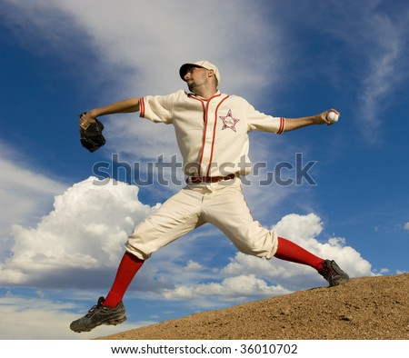 Baseball pitcher on pitcher's mound at full stretch about to release the ball. Set against a bright blue sky. Horiztonally framed shot.